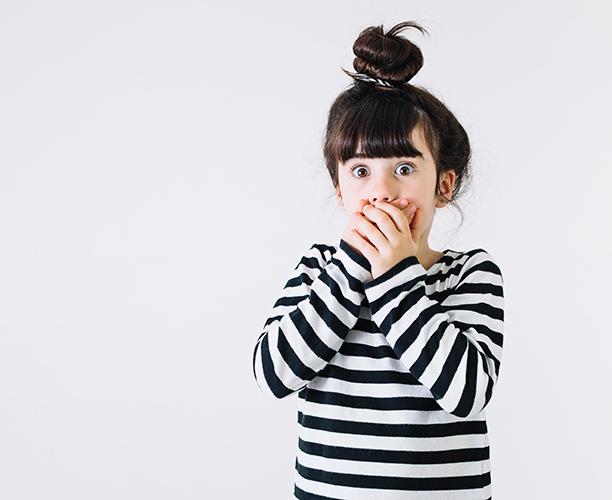 Девочка закрывает руками рот