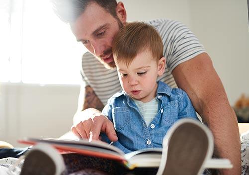Отец учит ребенка читать